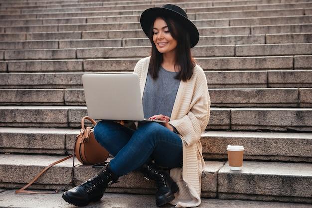 Portret van een glimlachende mooie vrouw die laptop computer met behulp van