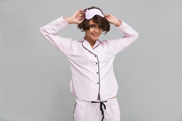 Portret van een glimlachende mooie vrouw die pyjama's draagt