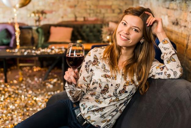 Portret van een glimlachende mooie vrouw met een glas wijn zittend op de bank