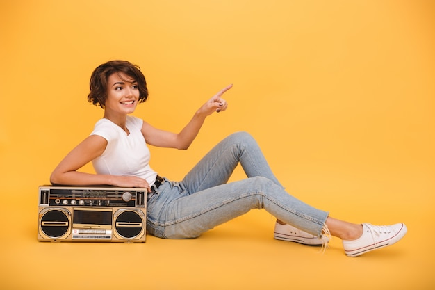 Portret van een glimlachende mooie vrouw zitten met platenspeler