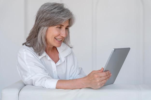 Portret van een glimlachende oudere vrouw die thuis een laptop gebruikt
