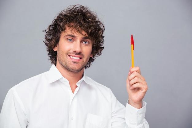 Portret van een glimlachende pen van de zakenmanholding over grijze muur