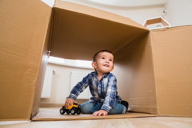 Portret van een glimlachende peuterjongen die met stuk speelgoed voertuigen speelt
