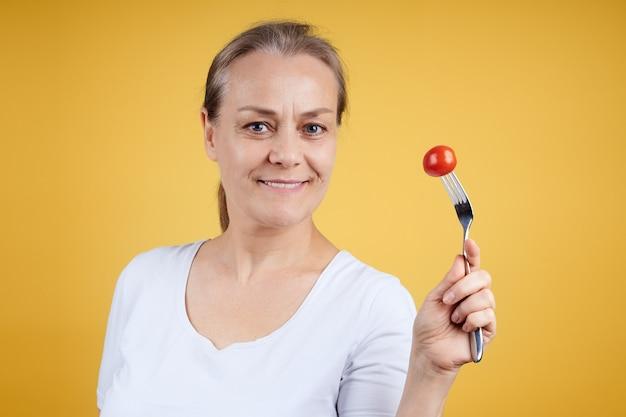 Portret van een glimlachende rijpe vrouw in een wit overhemd met een tomaat op een vork