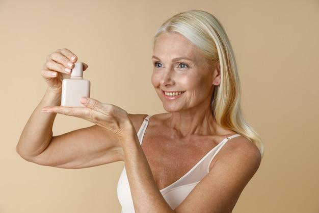 Portret van een glimlachende rijpe vrouw in ondergoed die wegkijkt en reclame vasthoudt en een witte pot vasthoudt