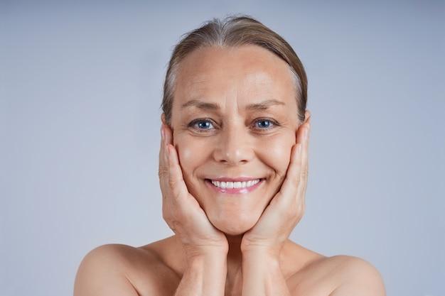 Portret van een glimlachende rijpe vrouw met haar handen op haar wangen.