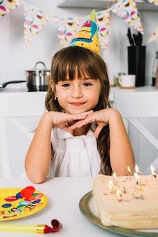 Portret van een glimlachende schattige verjaardag meisje met feest hoed op haar hoofd
