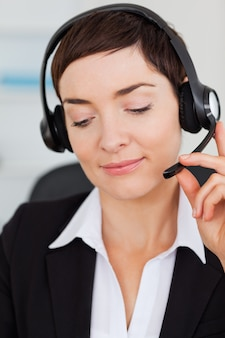 Portret van een glimlachende secretaresse die met een hoofdtelefoon roept
