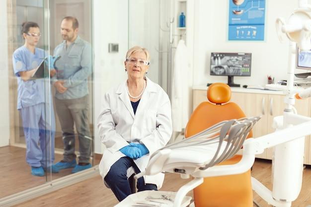 Portret van een glimlachende senior tandartsvrouw in de tandartspraktijk terwijl een medisch verpleegkundige met de patiënt op de achtergrond praat