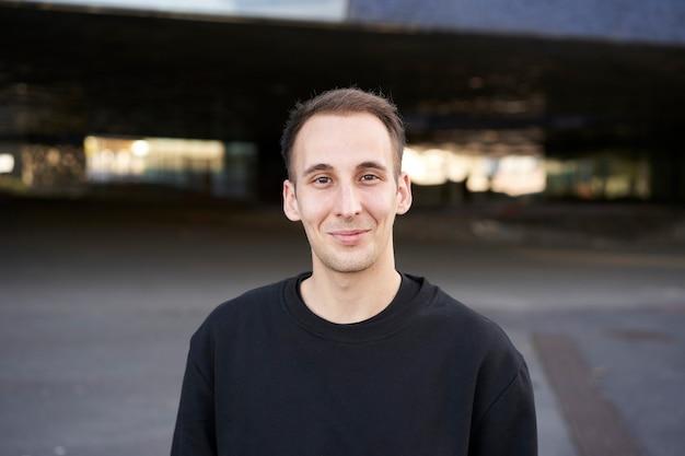 Portret van een glimlachende spaanse jonge man die naar voren kijkt