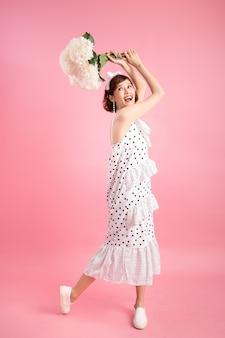 Portret van een glimlachende speelse leuke die bloemen van de vrouwenholding op roze worden geïsoleerd