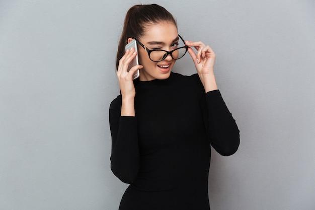 Portret van een glimlachende speelse vrouw in brillen
