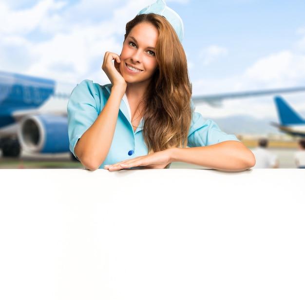 Portret van een glimlachende stewardess die een leeg paneel toont