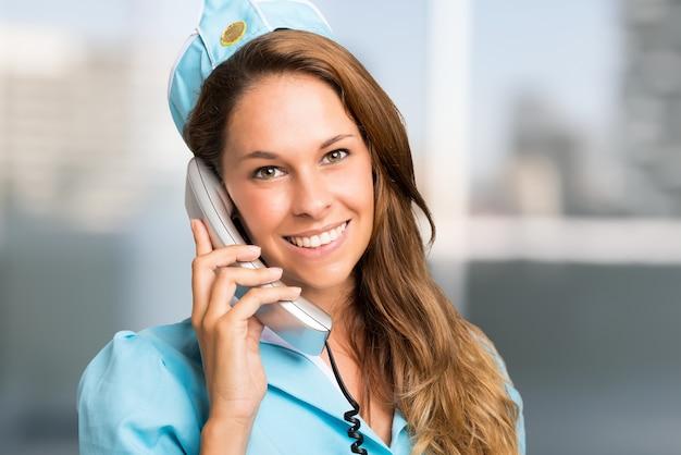 Portret van een glimlachende stewardess die op de telefoon spreekt