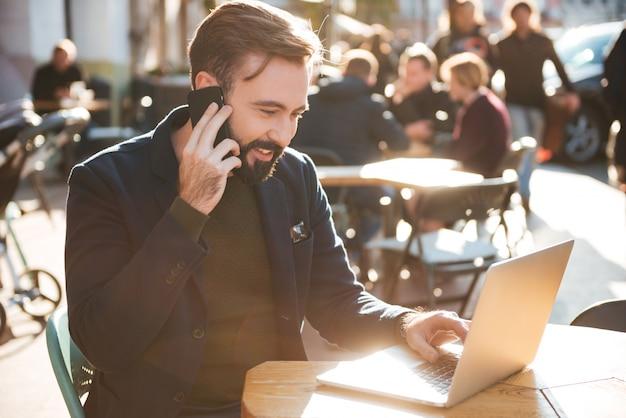 Portret van een glimlachende stijlvolle man aan het werk op laptop