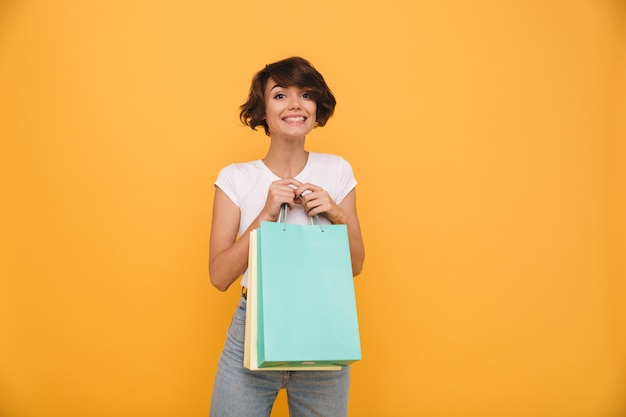 Portret van een glimlachende tevreden vrouwenholding het winkelen zakken