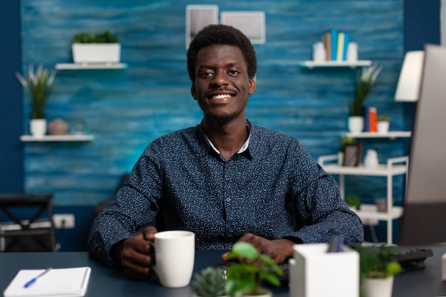 Portret van een glimlachende tiener die een kopje koffie vasthoudt terwijl hij studeert aan managementles met behulp van online universitaire klas tijdens coronavirusvergrendeling. zwarte man werkt op afstand van huis