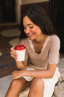 Portret van een glimlachende tiener die meeneemkoffiekop houdt