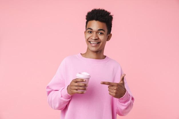 Portret van een glimlachende tienerjongen met een pullover die geïsoleerd over een roze muur staat, een koffiekopje vasthoudt en met de vinger wijst