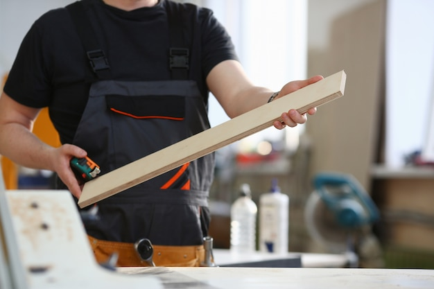 Portret van een glimlachende timmerman die houten planken houden