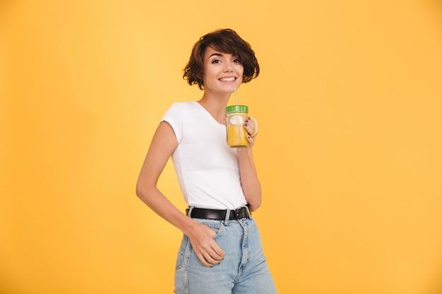 Portret van een glimlachende toevallige vrouw die sinaasappel drinkt