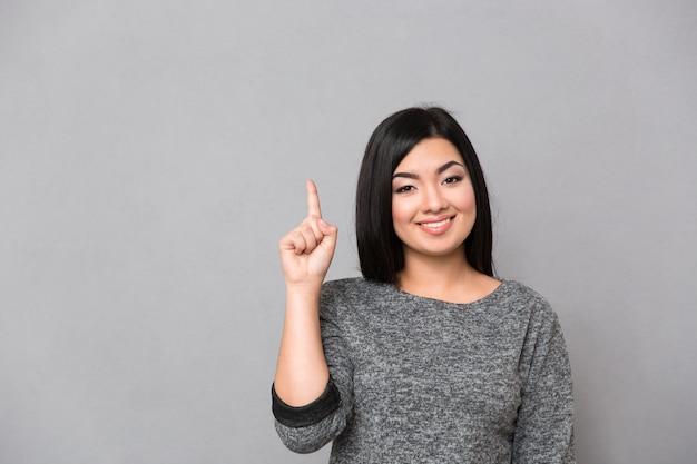 Portret van een glimlachende toevallige vrouw die vinger op grijze muur benadrukt