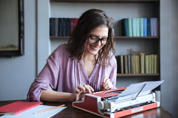 Portret van een glimlachende volwassen authoress zitten aan de tafel