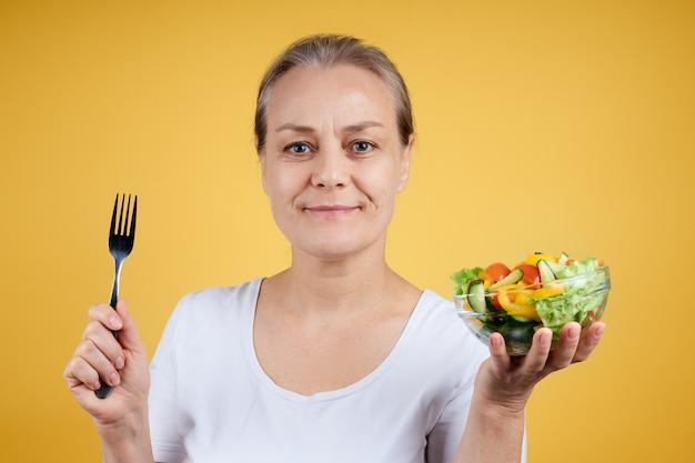 Portret van een glimlachende volwassen vrouw in een wit overhemd met een bord salade en een vork, klaar voor het avondeten