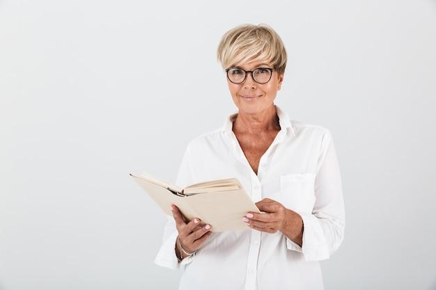 Portret van een glimlachende volwassen vrouw met een bril die een boek vasthoudt en naar een camera kijkt die over een witte muur in de studio wordt geïsoleerd;