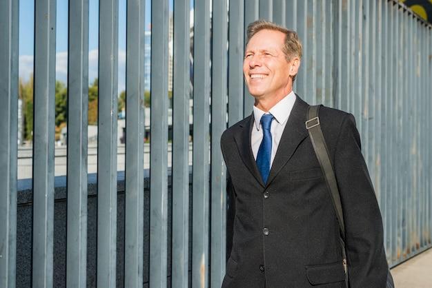 Portret van een glimlachende volwassen zakenman in openlucht