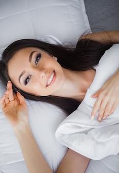 Portret van een glimlachende vrij jonge donkerbruine vrouw die in wit bed ontspant