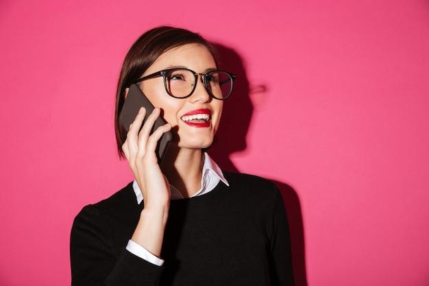 Portret van een glimlachende vrolijke onderneemster die op mobiele telefoon spreekt
