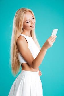 Portret van een glimlachende vrolijke vrouw die naar slimme telefoon kijkt die op de blauwe achtergrond wordt geïsoleerd