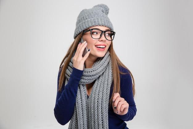 Portret van een glimlachende vrouw die aan de telefoon praat en wegkijkt geïsoleerd op een witte muur