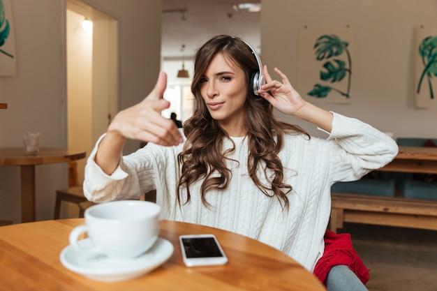 Portret van een glimlachende vrouw die aan muziek luistert