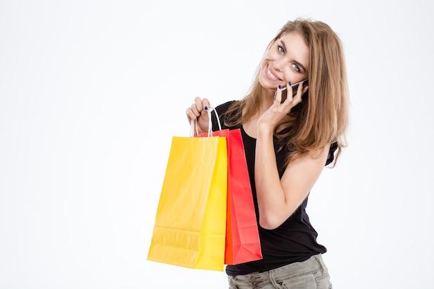 Portret van een glimlachende vrouw die boodschappentassen vasthoudt en aan de telefoon praat geïsoleerd op een witte achtergrond