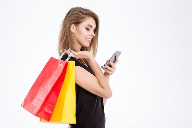 Portret van een glimlachende vrouw die boodschappentassen vasthoudt en smartphone gebruikt die op een witte achtergrond wordt geïsoleerd