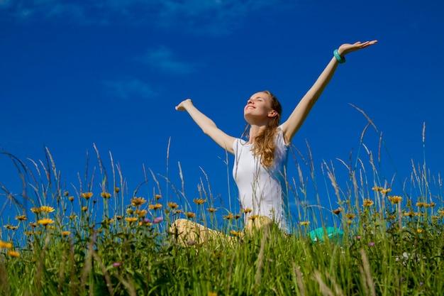Portret van een glimlachende vrouw die buiten zit met opgeheven handen en zich verheugt in de zon