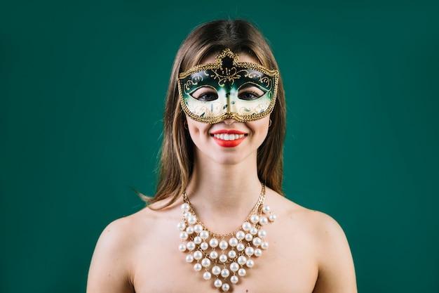 Portret van een glimlachende vrouw die carnaval-masker op gekleurde achtergrond draagt