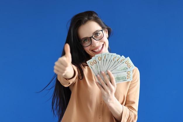 Portret van een glimlachende vrouw die contante dollars en duimen omhoog houdt