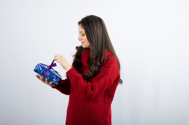 Portret van een glimlachende vrouw die een doos van de gift van kerstmis opent met paars lint.