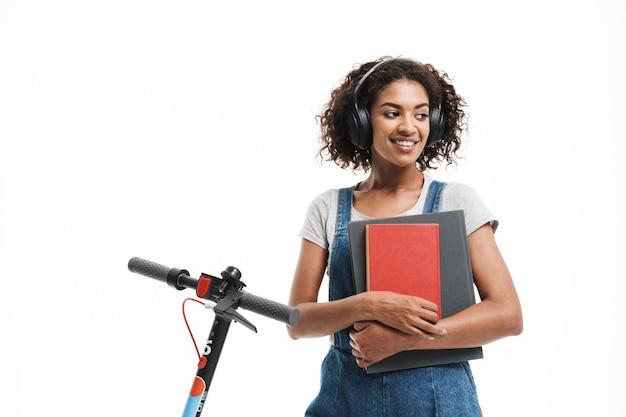 Portret van een glimlachende vrouw die een koptelefoon gebruikt en oefenboeken vasthoudt terwijl ze op een scooter rijdt, geïsoleerd over een witte muur