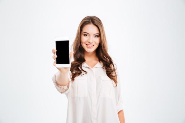 Portret van een glimlachende vrouw die een leeg smartphonescherm toont dat op een witte muur is geïsoleerd