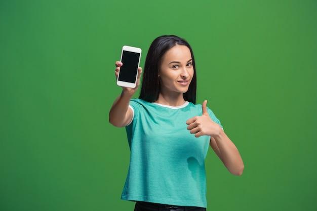 Portret van een glimlachende vrouw die het lege smartphonescherm toont dat op groen wordt geïsoleerd