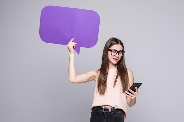 Portret van een glimlachende vrouw die lege toespraakbel toont en mobiele telefoon houdt die over grijze muur wordt geïsoleerd