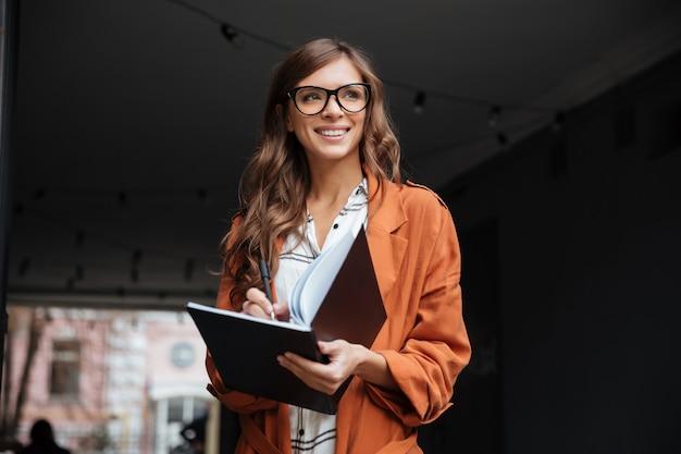 Portret van een glimlachende vrouw die nota's maakt
