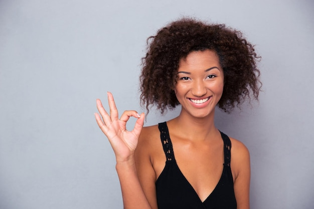 Portret van een glimlachende vrouw die ok teken met vingers over grijze muur toont en voorzijde bekijkt