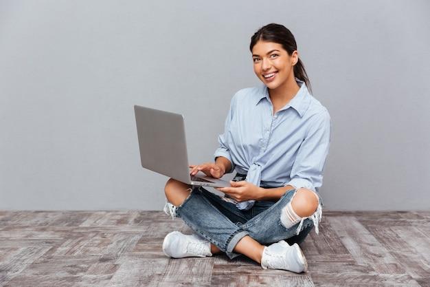 Portret van een glimlachende vrouw die op de vloer zit met een laptopcomputer op een grijze muur