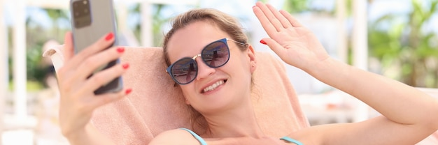 Portret van een glimlachende vrouw die op een ligstoel op het strand ligt en met haar hand zwaait in smartphone