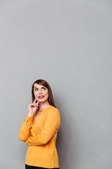 Portret van een glimlachende vrouw die op manier exemplaarruimte bekijkt die over grijze achtergrond wordt geïsoleerd